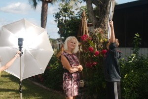 The portable umbrella/flash combination with the reflector being used as a scrim to cut the direct sun on the subject.